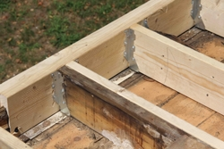 """New joists were """"sistered"""" along-side the original framing members and supported on the ends with metal hangers."""