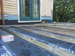 After new sheathing was installed, the roof was covered with a single sheet of EDPM rubber roofing. Then, Tapered 2x joists were installed to accommodate the slope of the roof.