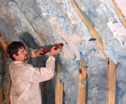 An installer uses a long reciprocating blade to cut the expanded SPF flush with the wall studs.