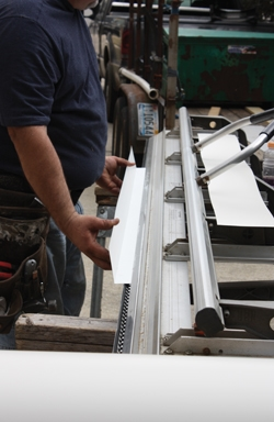 The aluminum trim wrap is fabricated on site to match the size and shape of the wooden window trim.