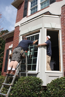 Large units require some assistance when installing. A worker on the inside lifts the window with a suction cup.
