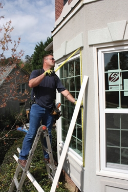 The windows are carefully measured to determine the length of the aluminum wrap.