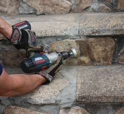 A drill-mounted wire brush can clean dirty masonry accurately and efficiently.