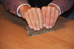 Hold the cabinet scraper with both hands at a low angle to the wood. The shape of the burr on the scraper allows approximately 0.02 millimeters of material to be removed at a time.