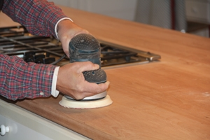 Start prepping the main counter wood surface with 80-grit to remove some of the stains that seeped into the wood. Work your way up to 220- grit sand paper.