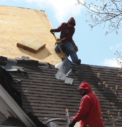The workers remove all the old roofing materials down to the deck.