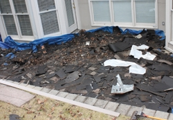 Tarps line the surrounding ground to collect roof debris.