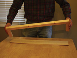 The plywood should fit snugly in the grooves along the top and bottom of the shelves.
