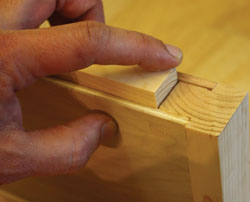 "Rip the ""ears"" off the grooved 2x stock to create the mounting cleat. Make sure the cleat fits inside the hollow shelf."