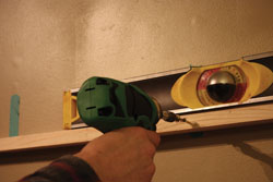 Level the cleat and screw into solid wall framing.