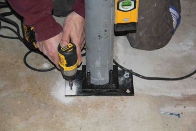 The bearing plate is fastened to the floor with concrete screws.