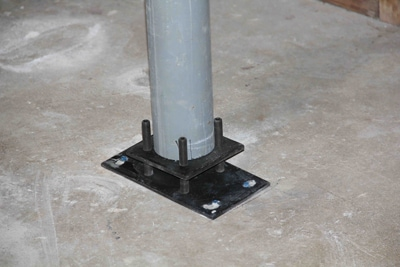 Once the adjustment screws are tightened, the adjustment plate lifts the column into place for final installation. The gap between the adjustment plate and bearing plate can then be filled with concrete of grout.