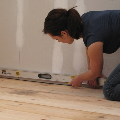 Find the highest spot in the floor where the cabinets will sit, then register your level line. The longer the level, the easier it is to get an accurate mark.