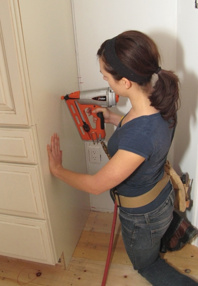 The wall-mounted cabinet gets a factory-finished, maple plywood end cap. Finish nails hold it tight, but be certain to drive them through the cabinet carcass only—and not into the body of the cabinet. Nails and clothes don't mix.