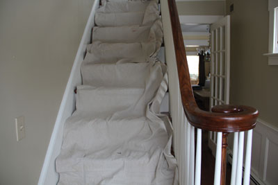 A canvas drop cloth makes a flexible and reusable protective cover for stairs surfaced with wood or carpet.