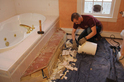 Bathroom demolition creates a substantial amount of garbage in the form broken drywall and shards of tile. Plan a way to dispose of the material in an orderly fashion.
