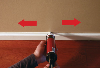 Hold the caulk gun at a 90-degree angle to strike a balance between pushing and pulling, and for easy visibility on both sides of the nozzle.