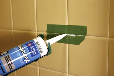 Waterproof caulk can be used to fill small cracks in tile grout.