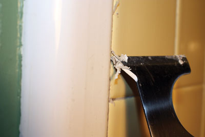 To remove old silicone caulk, cut the bead along each side with a utility knife and pull it from the joint. Carefully remove what remains with a paint scraper held at a shallow angle.