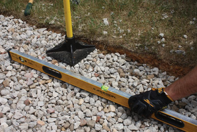 Tamp down and level the gravel bed.