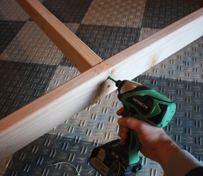 Screw the cross-members through the bed rails and into the end grain.