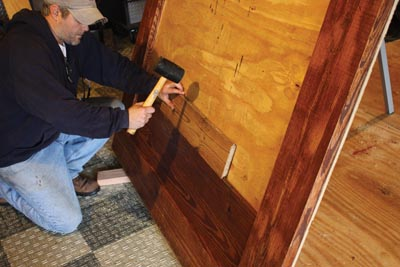 After turning the headboard upside-down, I was able to slide the T&G boards down into the rabbets and lock the joints together, fastening them with screws through the back of the plywood.