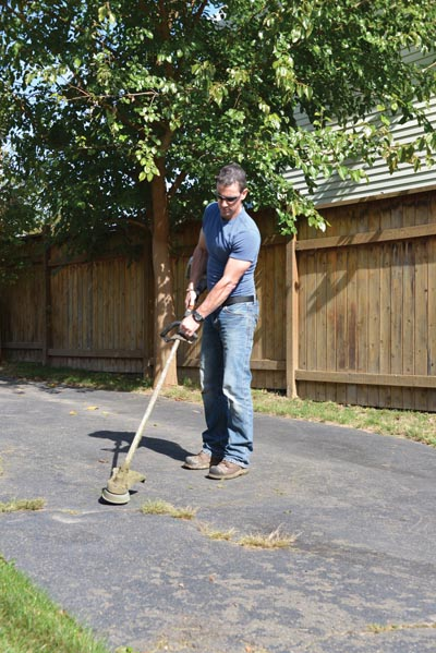 For weeds and grass in driveway cracks, try to pull out the plants by the root. If you can't get an adequate grip, then cut them down with a string trimmer and apply weed killer to the root system.