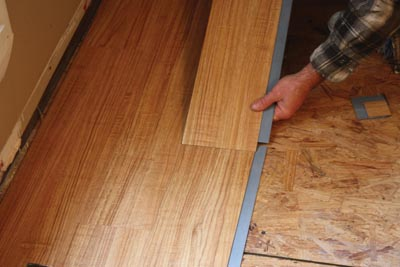 With vinyl planks, the adhesive strips on the ends are joined first.
