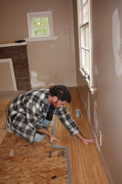 The adhesive strip along the long edge is then carefully pressed into place. Pro remodeler Richie Hamilton installs the flooring.