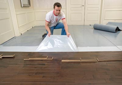 Lay out the Elastilon membrane on the subfloor, peel off the protective film, and press your wood flooring onto the sticky surface.