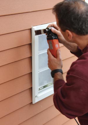 We used an oscillating multi-tool to carefully cut the siding to recess the door into the wall, giving it a more finished appearance and eliminating air gaps.