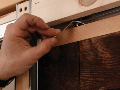 Install the stops so the doors kiss when they close. Leave your power tools out of this one, though. Just snug them up with a screwdriver. Use the world's smallest wrench to adjust the doors into plumb.