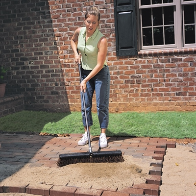 After placing the paver stones over the sand bed in your preferred pattern, sweep sand over the installation to fill the joints between pavers.