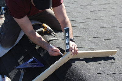 Use two pieces of wood to make a hinged angle finder. Use the angle finder on the roof ridge to determine the pitch.