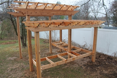 This two-level pergola includes framing for a bench or serving table.