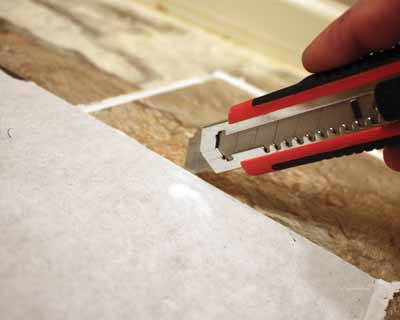 Vinyl tiles can easily be cut with a utility knife and a straight edge.
