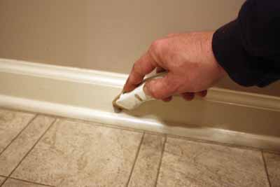 Cut the caulk joint of the shoe molding to avoid peeling paint.