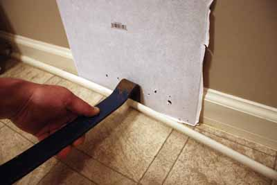 I open the joint with a paint scraper and then slip my flat bar inside to pry off the molding. A spare piece of tile protects the baseboard.