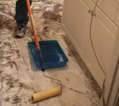 Multpurpose Floor Primer will help ensure a firm glue bond with the subfloor. I applied the primer with a paint roller.