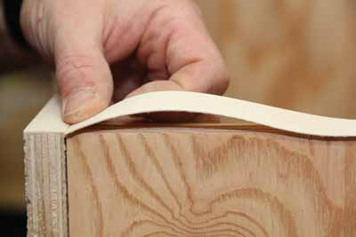 "To apply veneer tape between two existing pieces, heat the starting joint so it doesn't separate. Leave the opposite end of the tape unheated. Cut the end square and 1/64"" longer than the seam. Bow up your tape and tuck your seam tight to the edge of the intersecting tape."