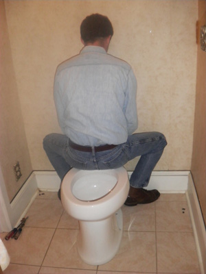 Use your body weight to press the toilet evenly over the gasket for a proper seal.