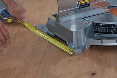 Measure the base of the miter saw to determine the width of the saw table.