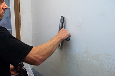 Monroe used a taping knife to apply a thin layer of joint compound on the wall.