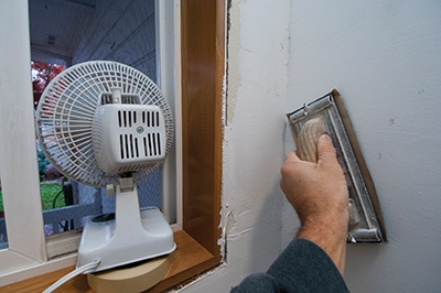 A hand sander was used to smooth out bumps and ridges in the finish. The sander holds precut sand paper. Notice the small fan positioned in the window to exhaust dust from the room.