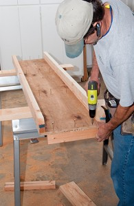 Turn the table over and use drywall screws to attach the wing board support blocks from the underside of the table.