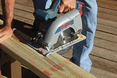 A cordless circular saw makes quick work of cutting deck boards to length.