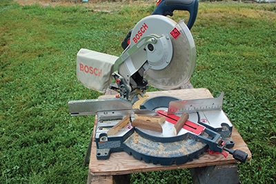 Trim boards are first routed to create a rounded edge, then cut to 45 degree angles to fit around awing posts. The Bosch cordless miter saw makes the on-site work easy.