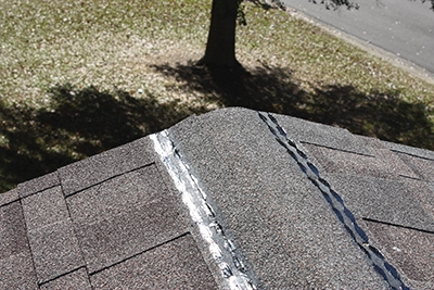 We installed shingles all the way to the ridge line then trimmed the excess at the top.