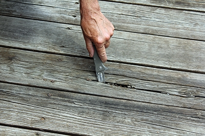 Many old boards had wide cracks and splinters. The first step was to test for any soft rotten spots.