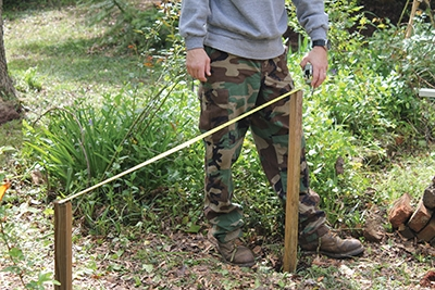 """Plumb """"marking posts"""" driven into the centers of each post hole help when taking measurements with a tape to ensure a square layout."""